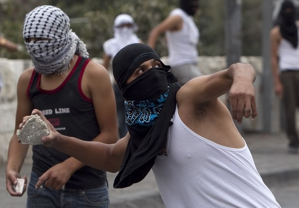 A Palestinian throws a stone at Israeli border police during clashes in the East Jerusalem neighbourhood of Silwan