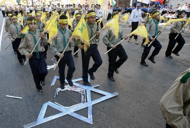 "Lebanon's Hezbollah al-Mahdi scouts carry Hezbollah flags as they parade on a Star of David symbol, during a rally marking ""Quds Day'' in Nabatieh town"