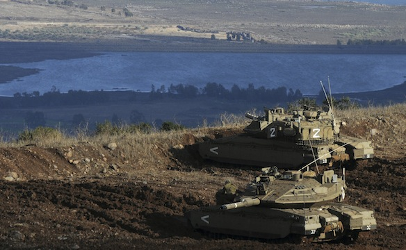 Israeli tanks stand in position overlooking Syrian village from the Israeli-occupied Golan Heights