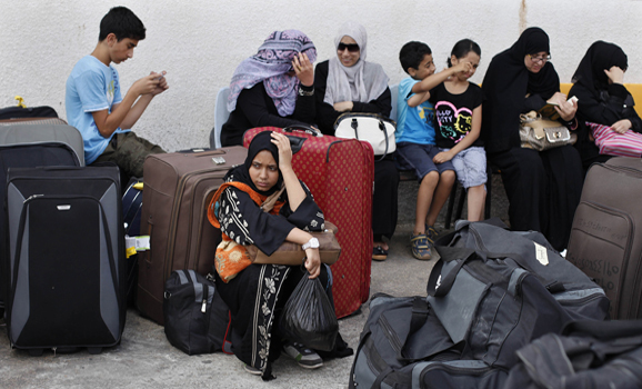 Palestinian passengers wait to cross into Egypt at Rafah border crossing in the southern Gaza Strip