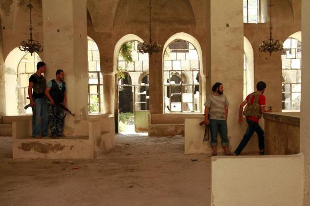 Members of the Free Syrian Army take cover inside a damaged Synagogue in the Bab al-Nasr neighborhood of Aleppo