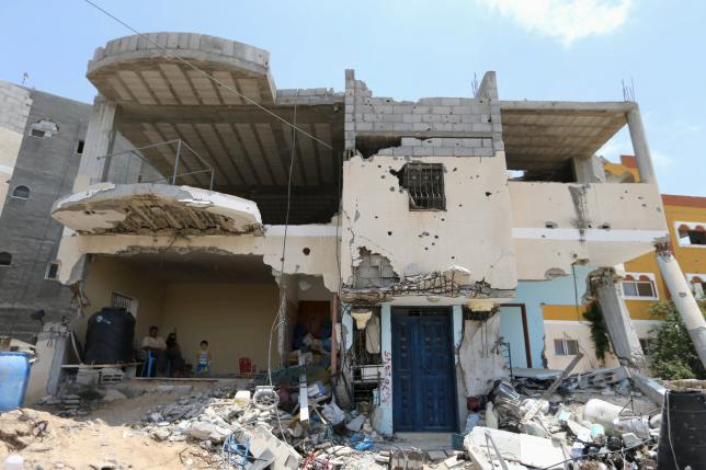 Members of a Palestinian family sit inside the remains of their house, that witnesses said was heavily damaged by Israeli shelling during a 50-day war last summer, in Khan Younis in the southern Gaza Strip